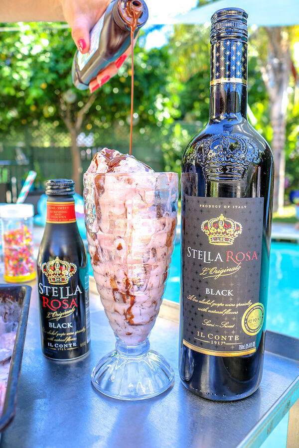 Dark desire ice cream served with Stella Rosa Black by the pool with chocolate syrup being poured on top.