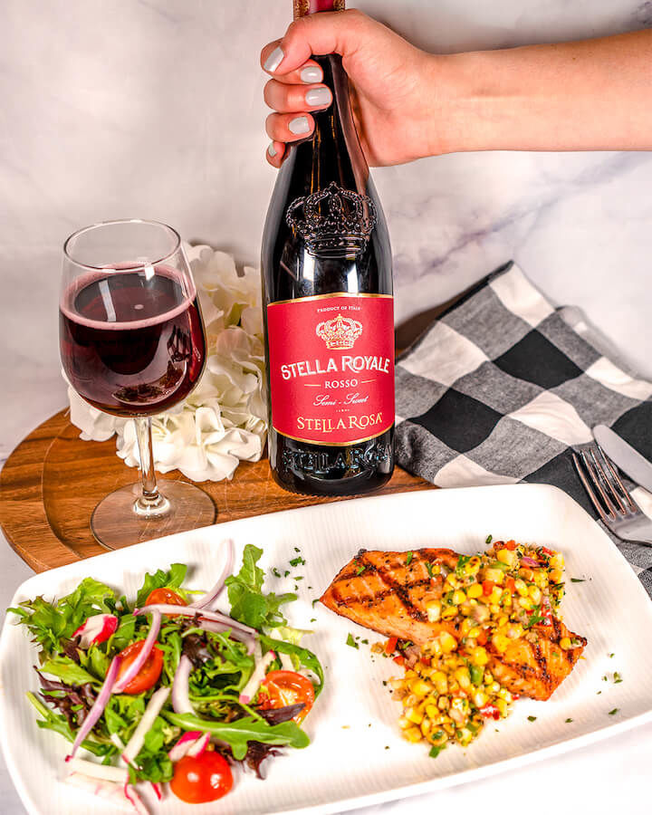 Hand holding the new Stella Rosa Royale with a glass of wine to the left and a plate with salad and the grilled salmon topped with corn relish with decorative flowers and napkins
