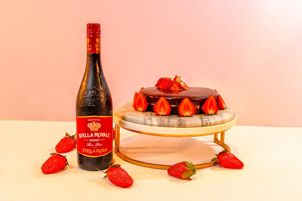 Red velvet cake topped fresh strawberries, served on a granite cake stand with Stella Rosa Royale.