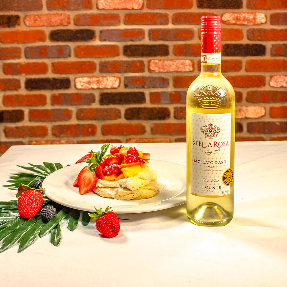 Pavlova cake topped with fruit served on a white plate next to a bottle of Moscato d'ASti.